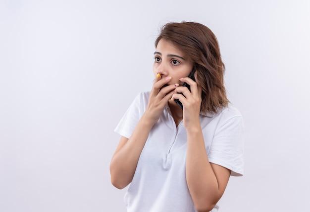 Giovane ragazza con i capelli corti che indossa una polo bianca scioccata mentre parla al telefono cellulare che copre la bocca con la mano