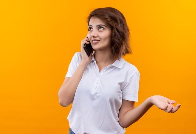 携帯電話で話している間笑顔の白いポロシャツを着た短い髪の少女
