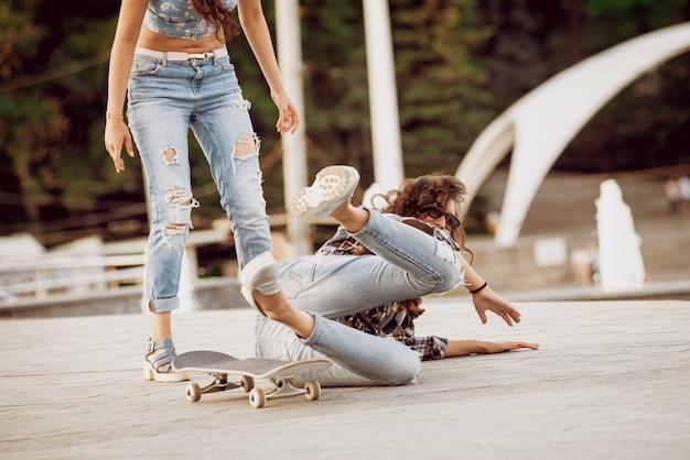 スケートボードを持つ少女、大きな灰色の壁の。