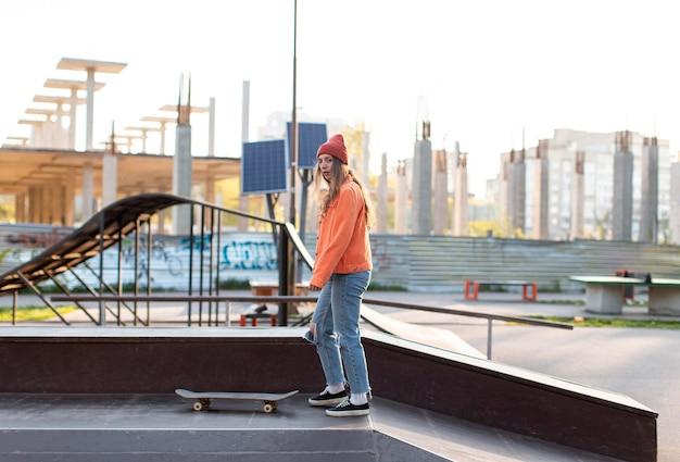 Молодая девушка с скейтбордом на открытом воздухе полный выстрел
