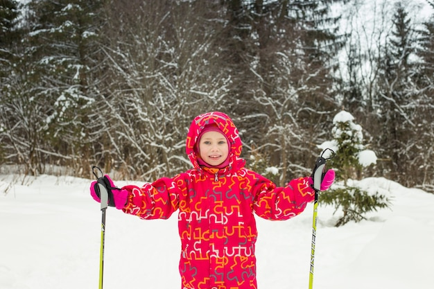 Young girl with ski in the snow forest