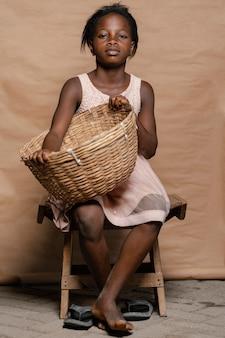 椅子に座っているわらのバスケットを持つ少女