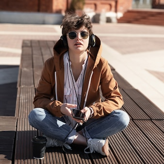 A young girl with a stylish short haircut sits on a bench and listens to music on headphones.