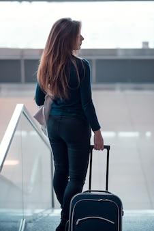 エスカレーターを下ってスーツケースを持つ少女。