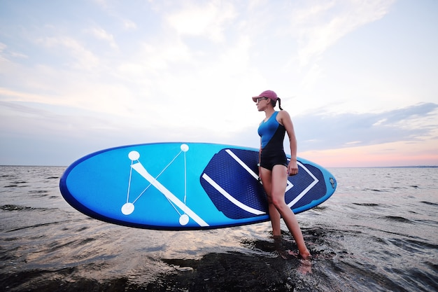Young girl with sup board on the background of the sea and sunset