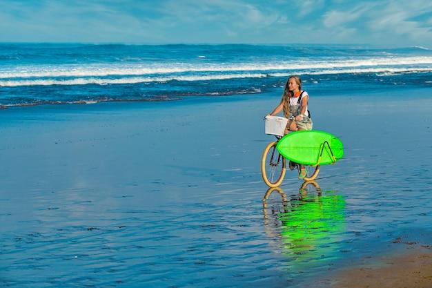 서핑 보드와 해변에 자전거 소녀