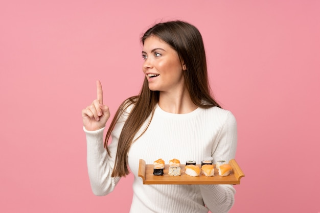 Young girl with sushi over isolated pink background intending to realizes the solution while lifting a finger up