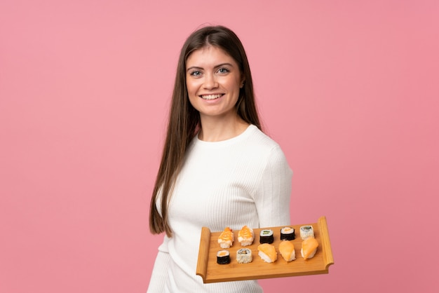 Young girl with sushi over isolated pink background smiling a lot