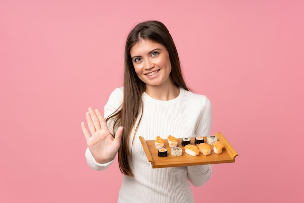 Young girl with sushi over isolated pink wall saluting with hand with happy expression