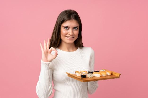 Молодая девушка с суши на розовом фоне, показывая хорошо знаком с пальцами