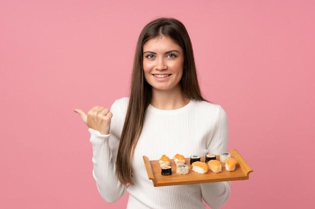 Молодая девушка с суши над розовым, указывая на сторону, чтобы представить продукт