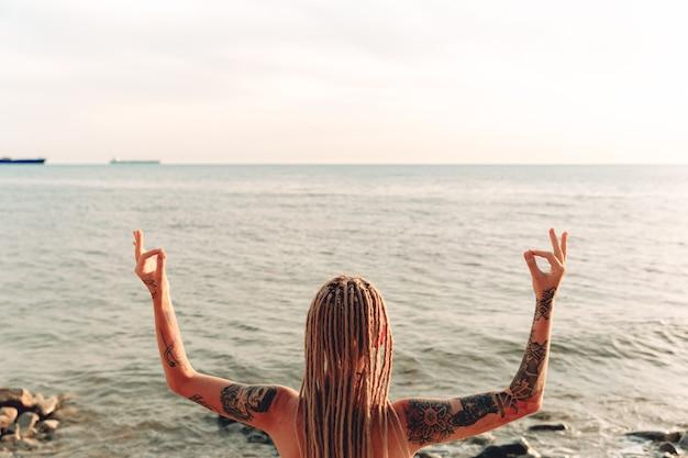 入れ墨の少女は海でヨガを練習します。瞑想のジェスチャー。後ろから見る