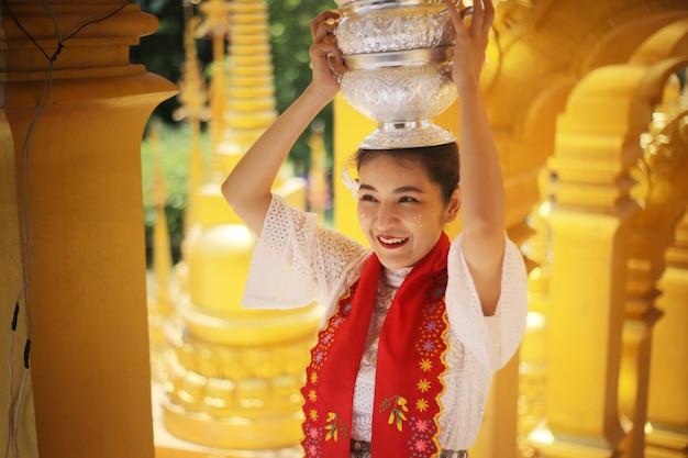 ミャンマーの美しい黄金の塔で手にご飯のボウルを保持している伝統的なビルマの少女