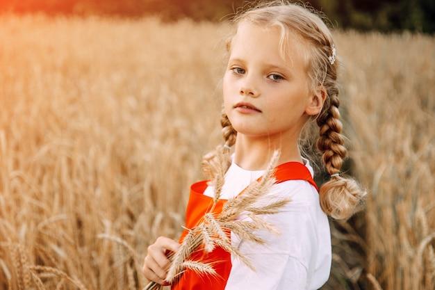 Молодая девушка с двумя косичками позирует в поле