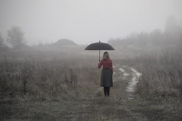 秋のフィールドで傘を持つ少女