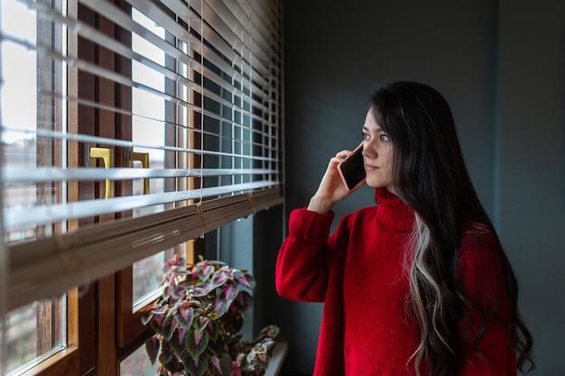 Молодая девушка с очень длинными волосами разговаривает по телефону, глядя в окно