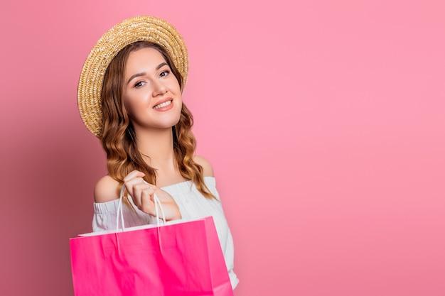 밀 짚 모자와 분홍색 벽에 분홍색 쇼핑 종이 봉지와 빈티지 드레스에 물결 모양의 머리를 가진 어린 소녀. 명랑 소녀 미소 구매하고 카메라를 본다