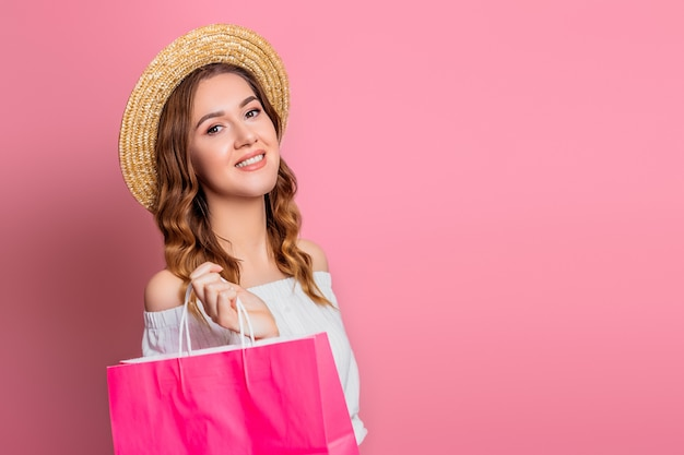 Young girl with wavy hair in a straw hat and vintage dress with a pink shopping paper bag on a pink wall . cheerful girl smiles makes purchases and looks at the camera