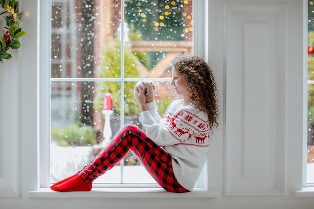 窓の近くに立っている冬のドレスの少女