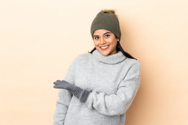 Young girl with winter hat on beige wall extending hands to the side for inviting to come