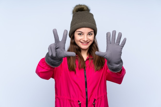 Young girl with winter hat on blue wall counting eight with fingers