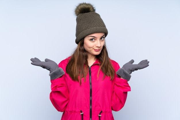 Young girl with winter hat on blue wall having doubts while raising hands