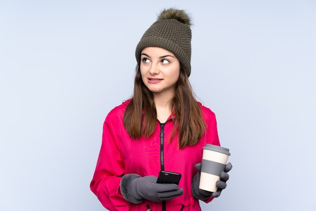 Young girl with winter hat on blue wall holding coffee to take away and a mobile while thinking something