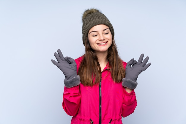 Young girl with winter hat on blue wall in zen pose