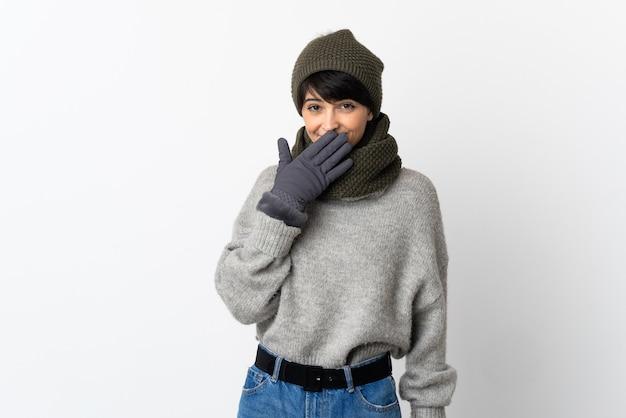 冬の帽子と幸せで笑顔の少女が手で口を覆う