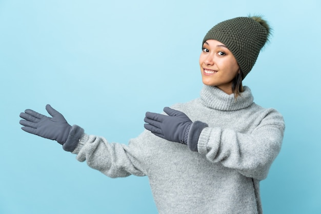 Young girl with winter hat isolated on blue extending hands to the side for inviting to come