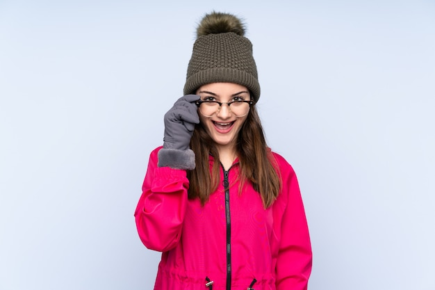 Young girl with winter hat isolated on blue with glasses and surprised