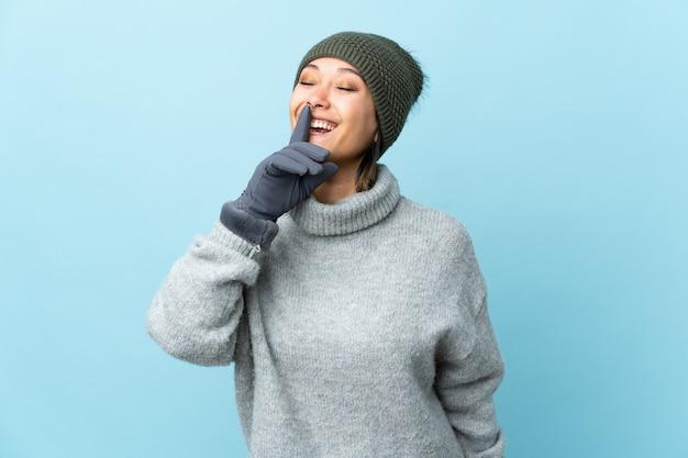 沈黙のジェスチャーをして青に分離された冬の帽子を持つ少女
