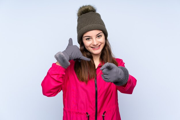파란색 전화 제스처를 만들고 앞을 가리키는에 고립 된 겨울 모자와 어린 소녀