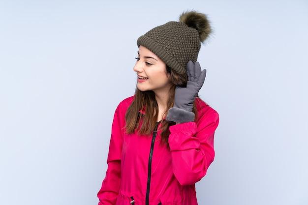 Молодая девушка в зимней шапке на синей стене слушает что-то, положив руку на ухо