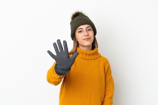 指で5を数える白い背景で隔離の冬の帽子を持つ少女