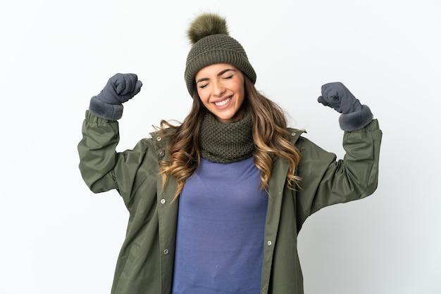 강한 제스처를 하 고 흰색 배경에 고립 된 겨울 모자와 어린 소녀