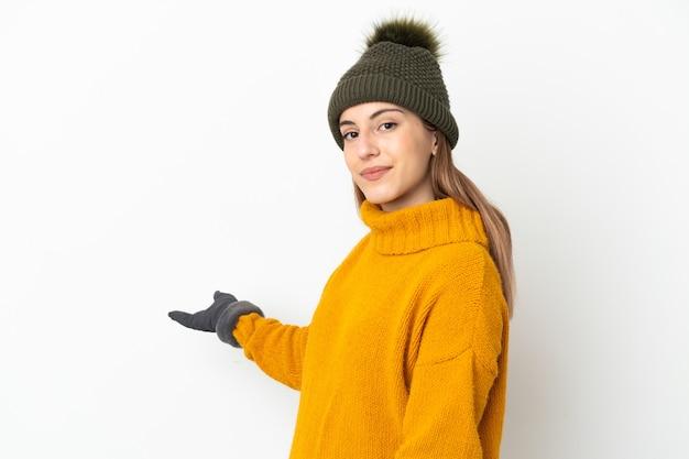 겨울 모자와 어린 소녀와 서 초대에 대 한 측면에 손을 확장 흰색 배경에 고립