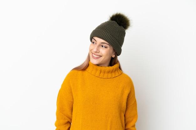 겨울 모자와 어린 소녀 측면을 찾고 웃 고 흰색 배경에 고립