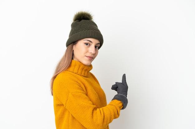 Молодая девушка в зимней шапке, изолированные на белом фоне, указывая назад