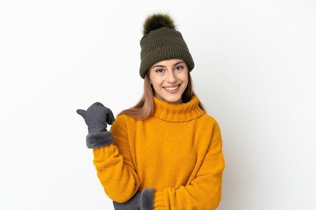 제품을 제시하기 위해 측면을 가리키는 흰색 배경에 고립 된 겨울 모자와 어린 소녀