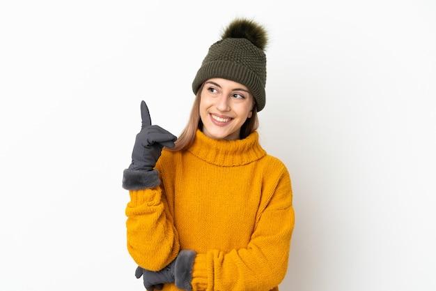 좋은 아이디어를 가리키는 흰색 배경에 고립 된 겨울 모자와 어린 소녀