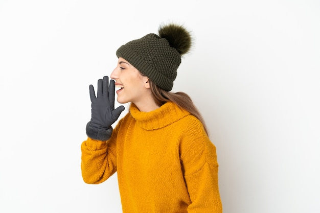 겨울 모자와 어린 소녀 흰색 배경에 고립 입 벌리고 측면에 외치는