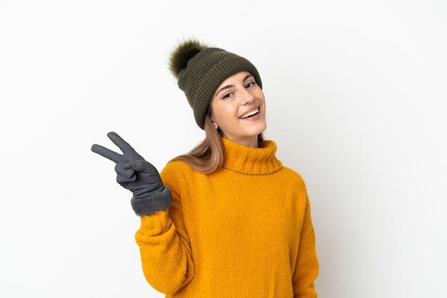 웃 고 승리 기호를 보여주는 흰색 배경에 고립 된 겨울 모자와 어린 소녀