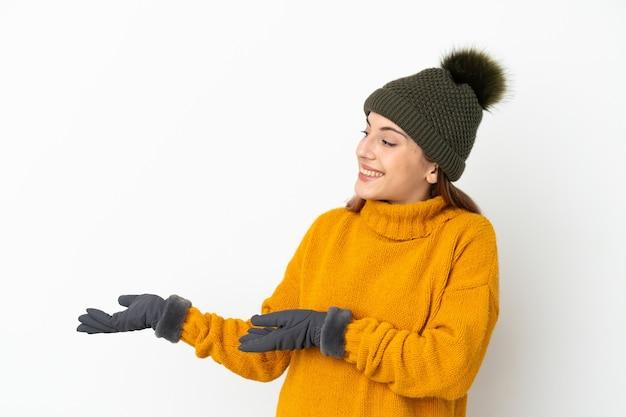 Молодая девушка в зимней шапке изолирована на белом фоне с удивленным выражением лица, глядя в сторону
