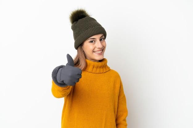 좋은 일이 일어났기 때문에 엄지 손가락으로 흰색 배경에 고립 된 겨울 모자와 어린 소녀