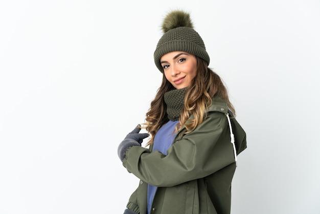 Молодая девушка в зимней шапке изолирована на белой стене, указывая назад