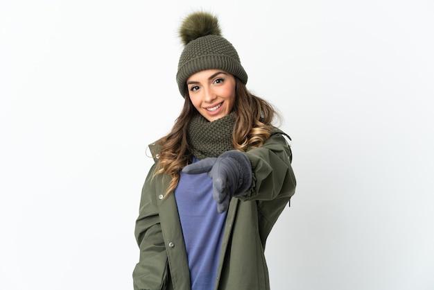 좋은 거래를 닫기 위해 악수하는 흰 벽에 고립 된 겨울 모자와 어린 소녀