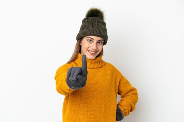 Молодая девушка в зимней шапке изолирована на белой стене, показывая и поднимая палец