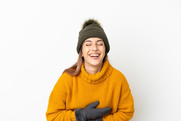 Молодая девушка в зимней шапке изолирована на белой стене, много улыбаясь