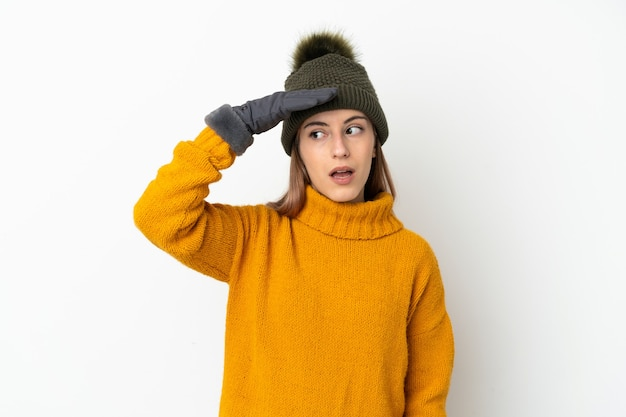 Young girl with winter hat isolated on white doing surprise gesture while looking to the side